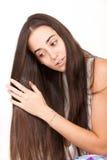 La mujer joven cepilla su pelo largo Imagenes de archivo