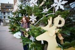 La mujer joven cerca adornó el árbol de navidad en una calle de Estrasburgo Imágenes de archivo libres de regalías