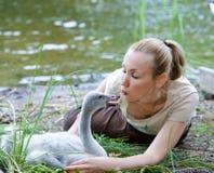 La mujer joven cerca de un pájaro de bebé de un cisne en el banco del lago Imagenes de archivo