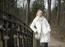 La mujer joven cerca de un puente en parque en la primavera temprana Fotografía de archivo libre de regalías