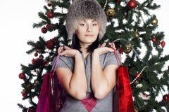 La mujer joven cerca del árbol del Año Nuevo hace compras Imágenes de archivo libres de regalías