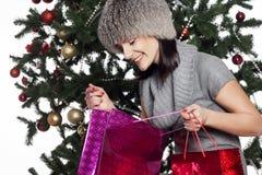 La mujer joven cerca del árbol del Año Nuevo hace compras Imagenes de archivo