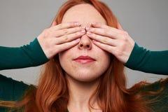 La mujer joven cierra ojos con dos manos Imagen de archivo libre de regalías