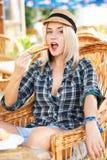La mujer joven come el croissant Foto de archivo