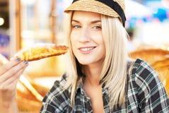 La mujer joven come el croissant Fotos de archivo libres de regalías