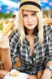 La mujer joven come el croissant Fotos de archivo