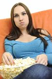 La mujer joven come las palomitas en el sofá anaranjado imágenes de archivo libres de regalías