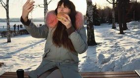 La mujer joven come una hamburguesa en la calle del invierno