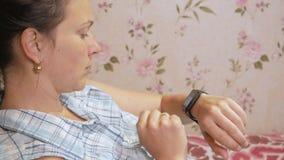 La mujer joven comprueba los mensajes en el smartwatch en casa en el sofá almacen de video