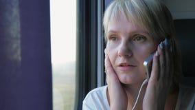 La mujer joven comunica por el teléfono, va en tren Siempre en tacto, concepto de la mujer de negocios almacen de video