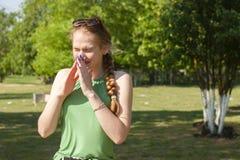 La mujer joven con alergia durante d?a asoleado est? limpiando su nariz imagenes de archivo