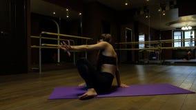 La mujer joven con la cola de caballo muestra la flexibilidad del cuerpo que hace el puente del ejercicio que dobla encima al rev metrajes