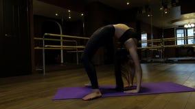 La mujer joven con la cola de caballo muestra la flexibilidad del cuerpo que hace el puente del ejercicio que dobla encima al rev almacen de metraje de vídeo
