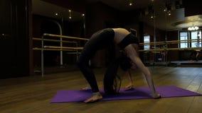 La mujer joven con la cola de caballo muestra la flexibilidad del cuerpo que hace el puente del ejercicio que dobla encima al rev almacen de video