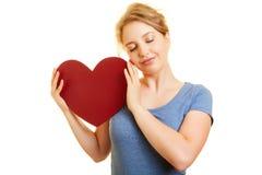 La mujer joven con el corazón rojo sueña sobre amor Foto de archivo