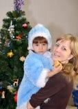 La mujer joven con el niño en un traje del soporte virginal de la nieve cerca de un árbol del Año Nuevo Fotografía de archivo
