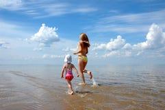La mujer joven con el niño runing en el agua Imagen de archivo libre de regalías