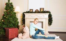 La mujer joven con el oso de peluche cerca de la chimenea en la Navidad adornó el interior de la casa Fotografía de archivo libre de regalías