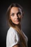 La mujer joven con el pelo largo en una chaqueta blanca contra fondo oscuro Fotos de archivo libres de regalías