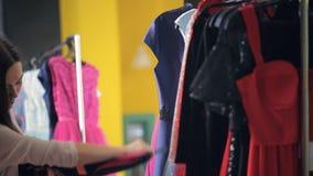 La mujer joven con el pelo oscuro largo, elige un vestido de una suspensión metrajes