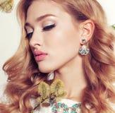 La mujer joven con el pelo rizado rubio lleva el vestido y la joya elegantes del cordón Fotos de archivo