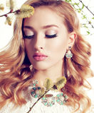 La mujer joven con el pelo rizado rubio lleva el vestido y la joya elegantes del cordón Imágenes de archivo libres de regalías