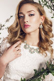 La mujer joven con el pelo rizado rubio lleva el vestido y la joya elegantes del cordón Imagen de archivo