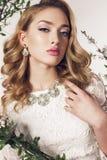 La mujer joven con el pelo rizado rubio lleva el vestido y la joya elegantes del cordón Foto de archivo