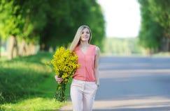 La mujer joven con el ramo de colores amarillos camina al aire libre imagenes de archivo