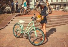 La mujer joven con el sombrero grande del verano y el vintage montan en bicicleta para el comienzo que espera de la travesía retr Foto de archivo