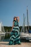 La mujer joven con el vestido y las gafas de sol del verano camina embarcadero de Marin Fotos de archivo