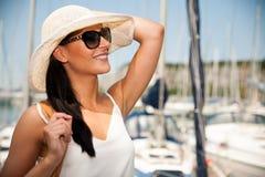 La mujer joven con el vestido y las gafas de sol del verano del sombrero camina embarcadero de m Imagenes de archivo