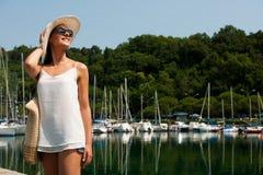 La mujer joven con el vestido y las gafas de sol del verano del sombrero camina embarcadero de m Imagen de archivo libre de regalías