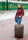 La mujer joven con equipaje está esperando un tren Imagen de archivo libre de regalías