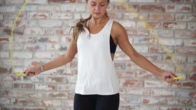 La mujer joven con la figura delgada está saltando enérgico con la cuerda en gimnasio metrajes