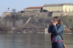 La mujer joven con la cámara retra del vintage toma las fotos Imagen de archivo libre de regalías