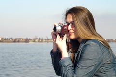 La mujer joven con la cámara retra del vintage toma las fotos Fotos de archivo