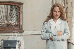 La mujer joven con la cara con las pecas y con el libro en sus manos está colocando contrario de una pared gris Fotos de archivo libres de regalías