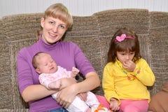 La mujer joven con la hija de tres años y el SIS del bebé en un sofá Imagen de archivo libre de regalías