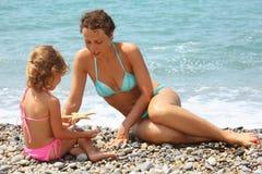 La mujer joven con la muchacha jugó estrellas de mar en la playa Fotografía de archivo libre de regalías