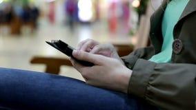 La mujer joven con la tableta se sienta en banco en alameda de compras almacen de video