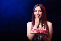 La mujer joven con la torta de cumpleaños en el partido Imagenes de archivo