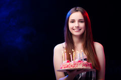 La mujer joven con la torta de cumpleaños en el partido Fotografía de archivo libre de regalías