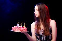 La mujer joven con la torta de cumpleaños en el partido Foto de archivo