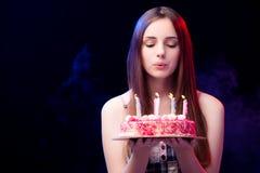 La mujer joven con la torta de cumpleaños en el partido Imágenes de archivo libres de regalías