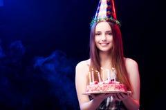 La mujer joven con la torta de cumpleaños en el partido Fotografía de archivo