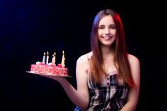 La mujer joven con la torta de cumpleaños en el partido Fotos de archivo libres de regalías