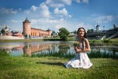 La mujer joven con las flores en vestido ligero se sienta en la hierba fotos de archivo