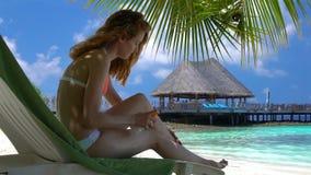 La mujer joven con las piernas hermosas utiliza la protección solar en la playa tropical Cámara lenta almacen de video
