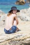 La mujer joven con las tetas al aire en sombrero y pantalones cortos se sienta en roca Foto de archivo